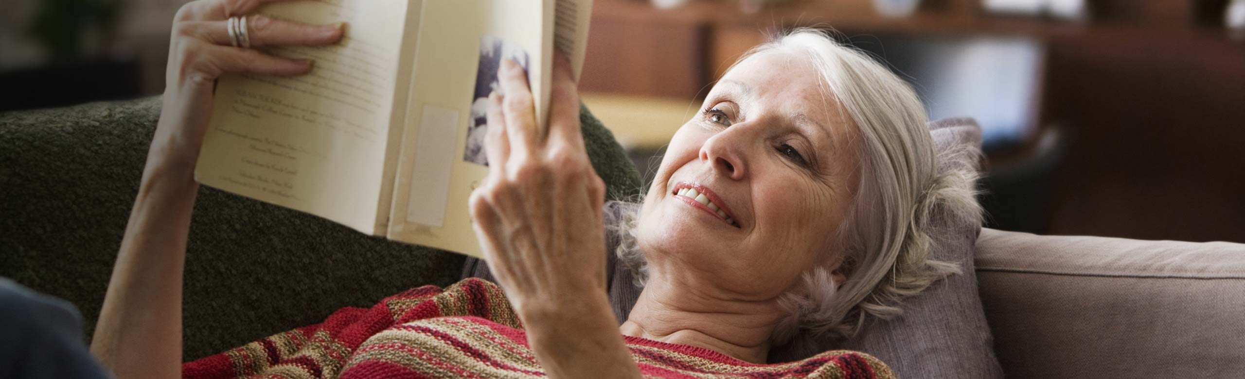 Woman laying on couch reading book