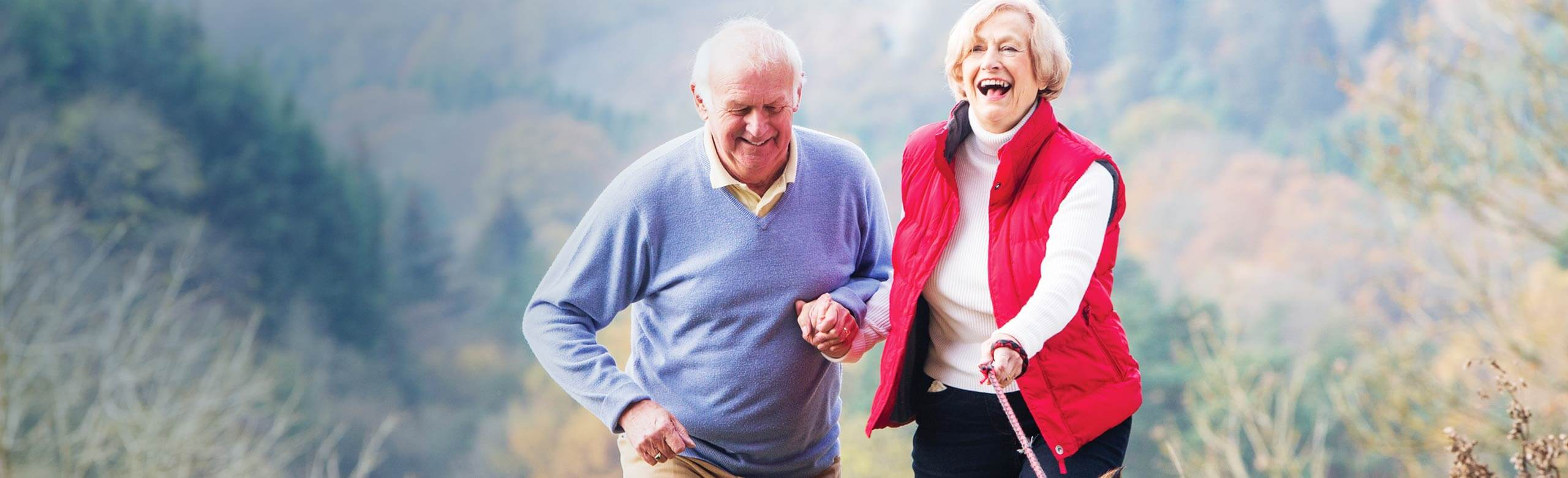 Man and woman walking outside while holding hands and laughing